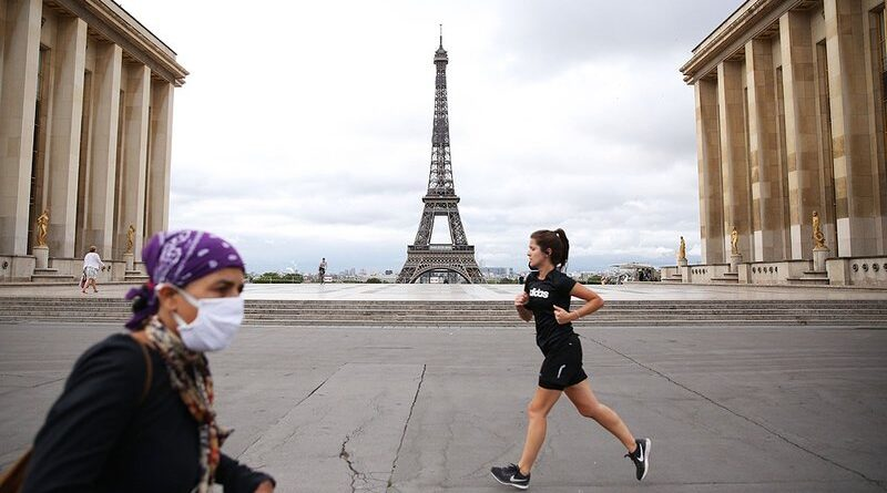 Mujer corriendo y otra con barbijo en Paris