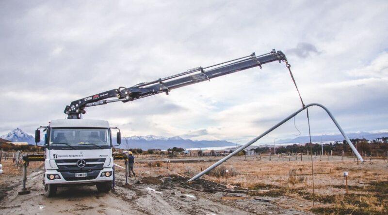 Maquinaria y trabajadores colocan postes de alumbrado público en la urbanización General San Martín, Ushuaia