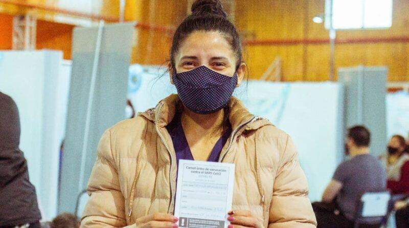 Mujer exhibe certificado de vacunación covid