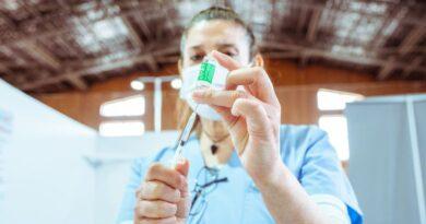 Personal de salud con vial de vacuna contra el covid y jeringa