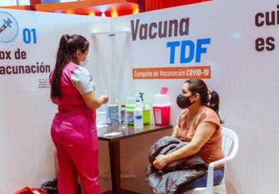 Personal de salud con vacuna junto a mujer en box de vacunación