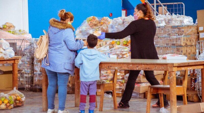Madre e hijo retiran mercadería del módulo alimentario de comedores escolares